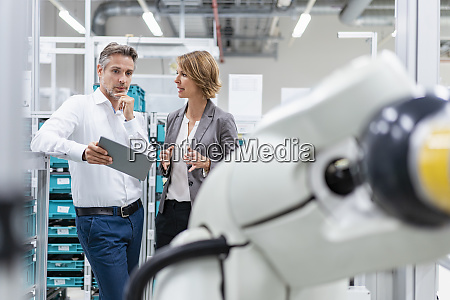 businesswoman and man with tablet talking