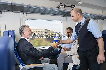 dirigent serviert einem zugpassagier kaffee