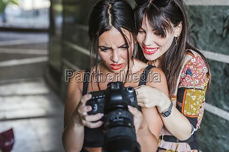 zwei junge frau ueberprueft fotos auf