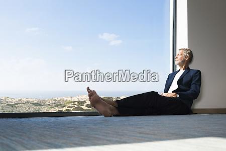 senior businessman sitting at panorama window