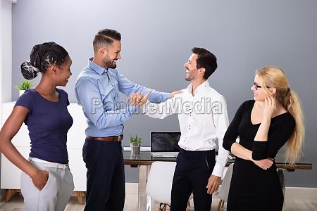 geschaeftsleute schuetteln haendeimt im besprechungsraum