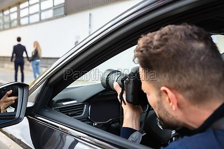 privatdetektiv macht fotos von mann und