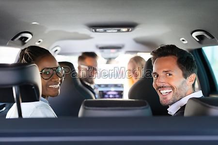 glueckliche freunde sitzen im auto und