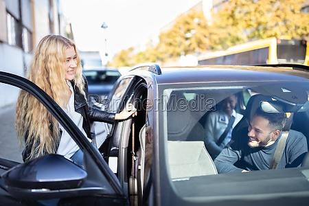 frau sitzt im auto mit freunden