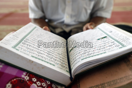alter mann lesen koran sitzend auf
