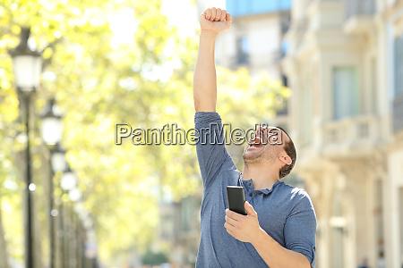 aufgeregter erwachsener mann haelt telefon feiert