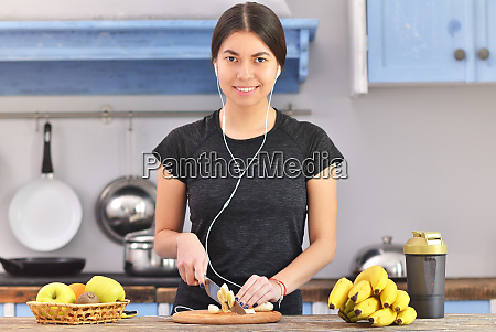 young woman preparing protein shake at