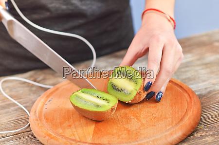 young woman in sportswear cutting kiwi