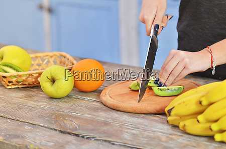 cropped view of girl cutting tasty
