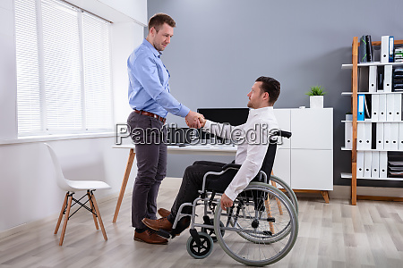 businessman on wheelchair shaking hand with