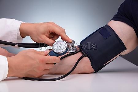 nahaufnahme des arztes kontrolle des blutdrucks