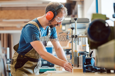 absorbed carpenter at the milling machine