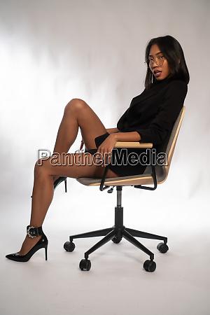 attraktive junge asiatische geschaeftsfrau sitzt auf