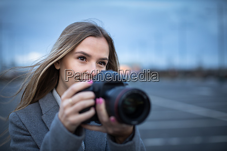 pretty young woman taking photos with