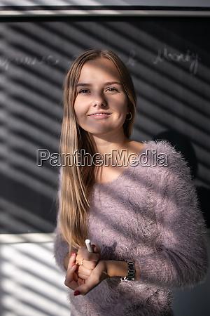 huebsche junge studentinlehrerin vor einer tafel