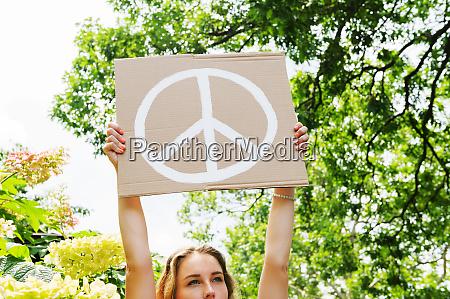 young woman holding aloft peace symbol