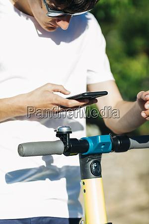 junger mann mit smartphone auf elektroroller
