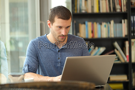 ernster mann mit einem laptop in