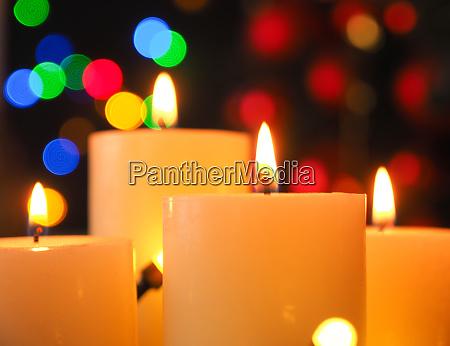 vier brennende adventskerzen mit weihnachtsbeleuchtung