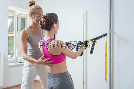 frau mit schlingentrainer waehrend der physiotherapie