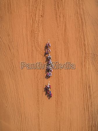luftaufnahme eines kamelrennens in der wueste