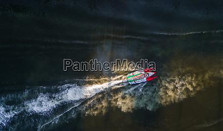 luftaufnahme eines schnellbootes waehrend eines rennens