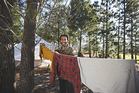 portrait happy man hanging laundry on