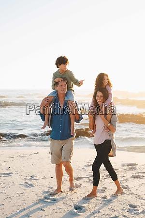 couple giving children piggyback ride on