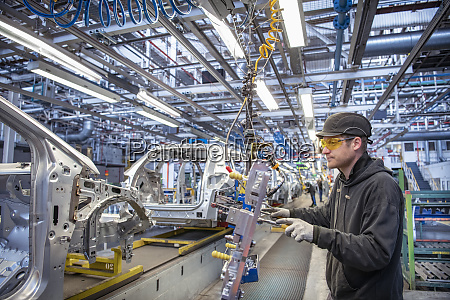 car worker fitting parts on production