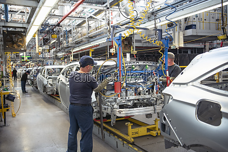 car workers fitting bonnets to cars