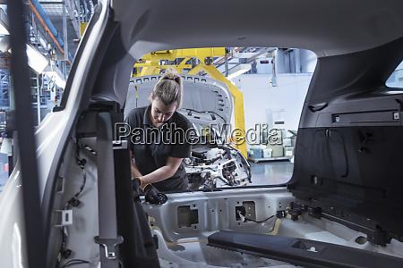 female worker assembling car interior on
