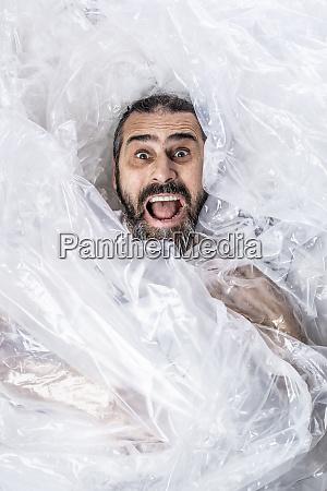portraet eines baertigen mannes in plastikfolienverpackung