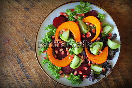 gesunder vegetarischer salat gebratener kuerbis tomate