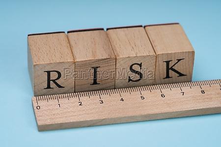 risikowort auf holzbloecken hinter dem lineal