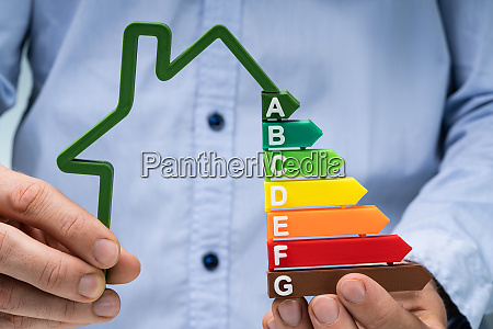 person holding green house energieeffizienz graph