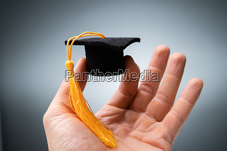 persons hand holding of black graduation