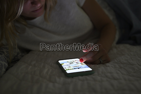 frau scrollt nachts auf dem smartphone