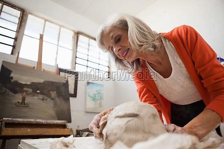 aufmerksame seniorin formt einen geformten ton