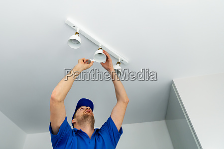 electrician installing led light bulbs in