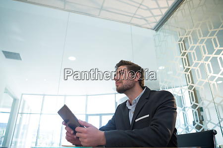 thoughtful businessman using digital tablet at