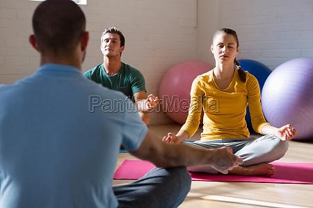 yogalehrer fuehrt schueler in meditation im