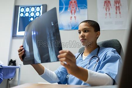 doctor examining x ray report at