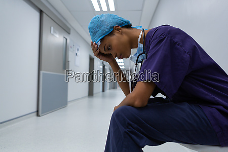 tensed surgeon with hand on forehead