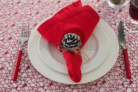 tannenzapfen und serviette auf einem teller