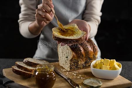 frau auftragen marmelade ueber multigrain brotscheibe