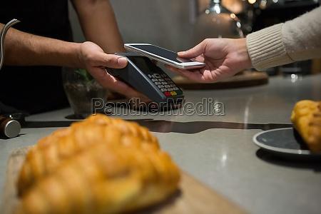 frau bezahlt rechnung per smartphone mit