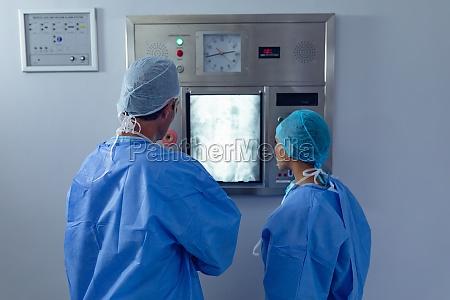 surgeons examining x ray on x
