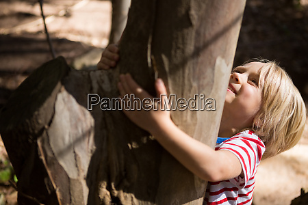 happy little girl hugging tree trunk