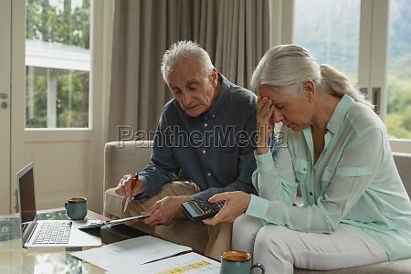 aktives seniorenpaar berechnet rechnungen im wohnzimmer