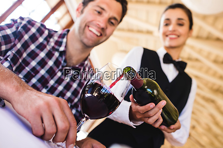 kellnerin giesst rotwein in weinglas am